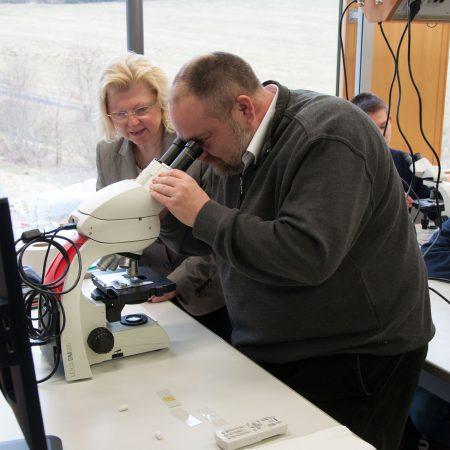 Geschäftsführer Roos inspiziert das Lehrermikroskop