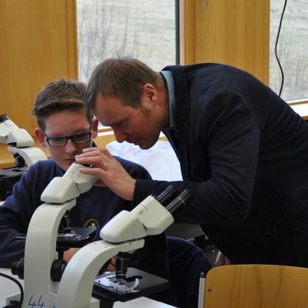 Schulleiter Weigand lässt sich das Schülermikroskop erklären