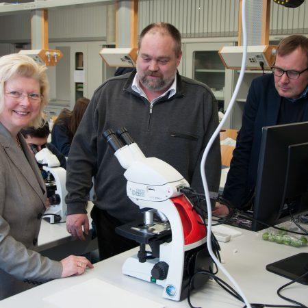 Glückliche Lehrerin demonstriert die Möglichkeiten des neuen Geräts